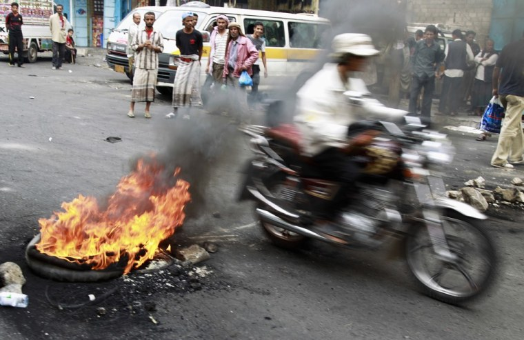 Image: A motorcyclist rides through a roadblock set up by anti-government protesters on a street in the southern Yemeni city of Taiz