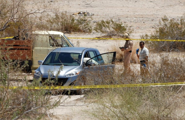 Image: Investigators check a vehicle thought to be that of a man suspected of shooting five people