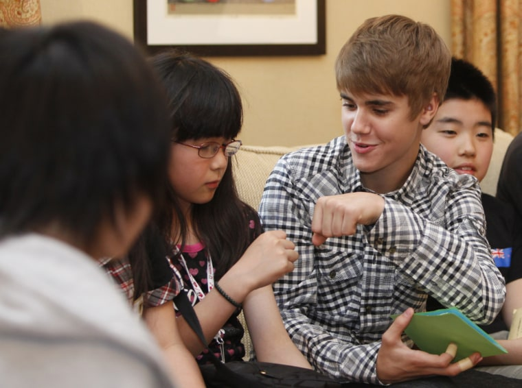 Image: Canadian pop star Bieber fist bumps with a girl from northeastern Japan