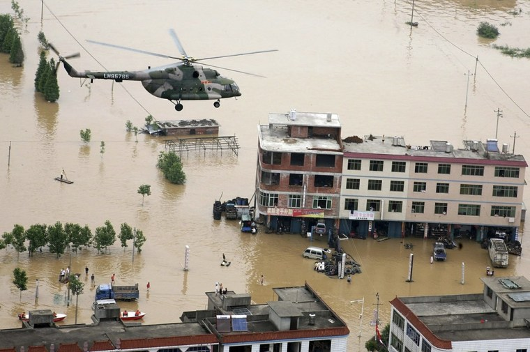 Image: a military helicopter flies over a flooded area in Fuzhou in China's Jiangxi province