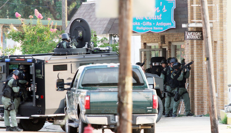 Louisiana State Police SWAT team members respond to the scene of a double-homicide at an insurance agency on West Main Street in downtown Ville Platte, La.