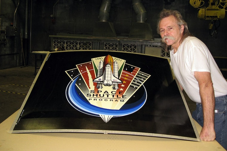 "Lockheed Martin graphic artist Jon Irving displays the ""nose art"" to be installed on the final space shuttle's external tank."