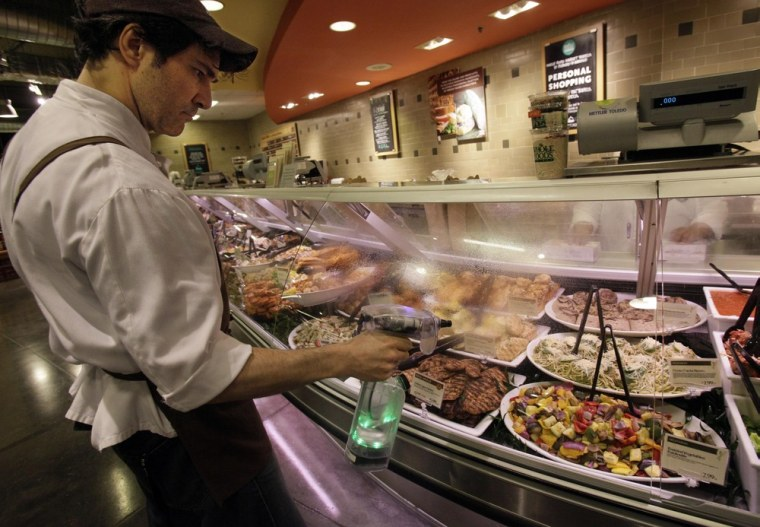 Image: Robert Fente cleans a glass case at the Whole Foods Market in New York with an ionized sprayer.