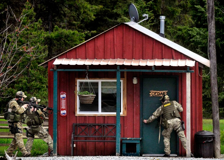 Missoula County sheriff's deputies sweep a rental cabin at the Lumberjack Saloon west of Lolo, Mont.
