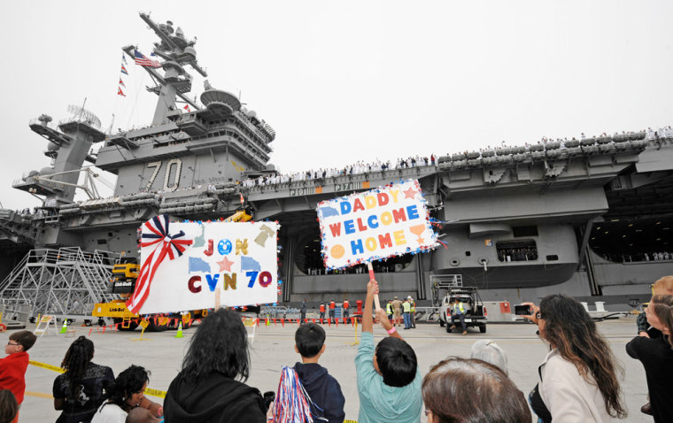 Image: Family members hold up welcome signs as the USS Carl Vinson aircraft carrier returns to its homeport at Naval Station North Island in Coronado