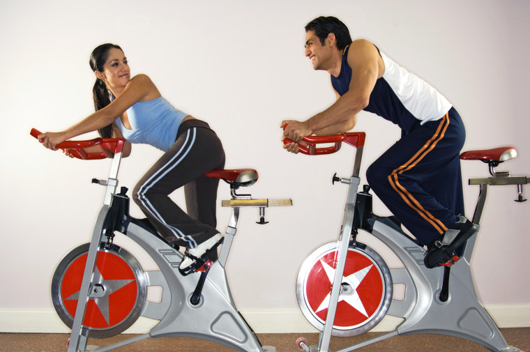 Image: Young man and woman on exercise bikes