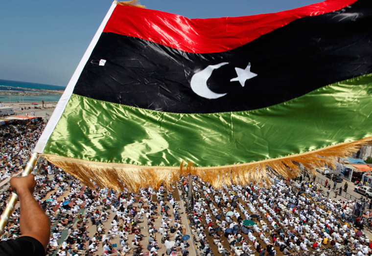 Image: A Libyan waves a Kingdom of Libya flag during Friday prayers near the courthouse in Benghazi