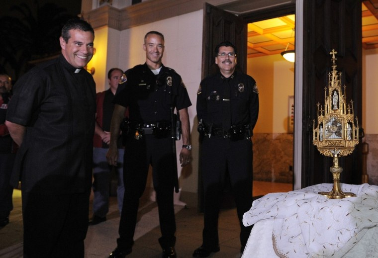 Image: Father Jose Magana, Long Beach police officer Jeff Liberman, and chief Robert Luna look at a 780-year-old religious relic after it was recovered