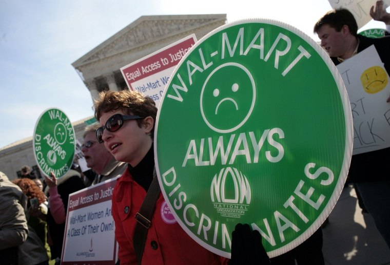 Image: File photo of protesters holding signs in front of the Supreme Court while class action lawsuit Dukes v. Wal-Mart is being argued inside the court in Washington