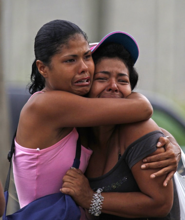 Image: Inmates' relatives embrace as they cry outside of El Rodeo I prison
