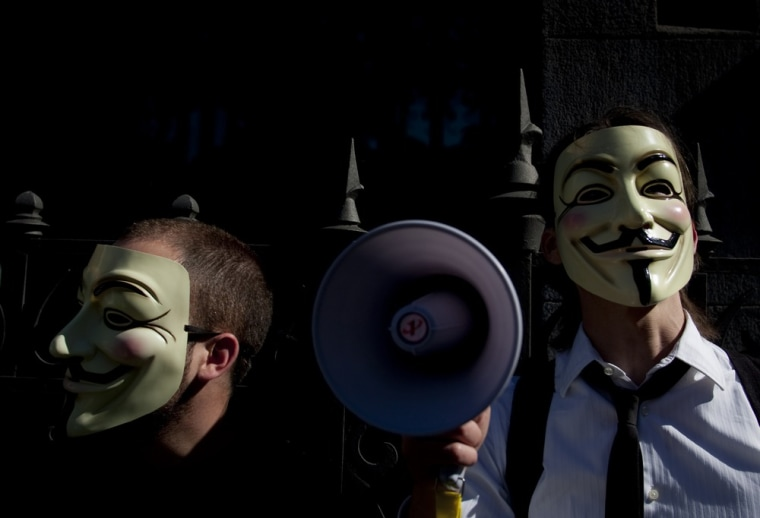 """Image: People wearing masks often used by a group that calls itself """"Anonymous""""  take part in a rally in Madrid"""
