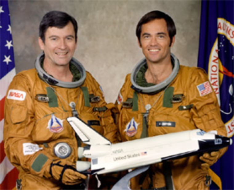 John Young, left, and Robert Crippen pose in their ejection escape suits with a model of space shuttle Columbia before their historic launch in 1981.