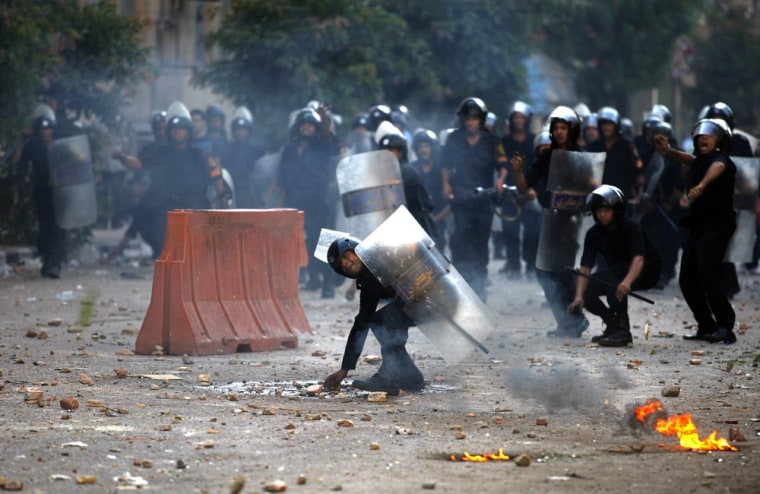 Image: Egyptian riot police throw stones at demonstrators during clashes close to the interior ministry in Cairo