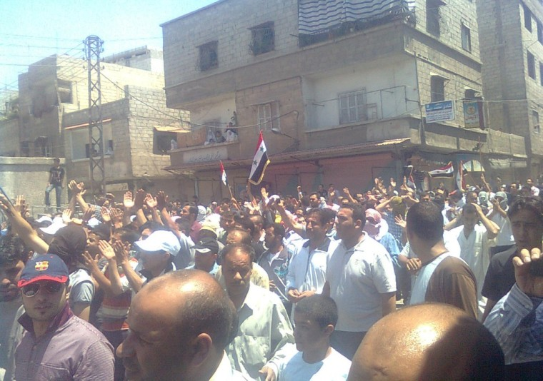 Image: Demonstrators march through the streets after Friday prayers in the Hajar Al Asswad in Damascus