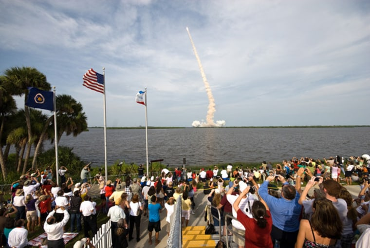 Crowds fill Kennedy Space Center's Banana River viewing site to see and record space shuttle Endeavour as it roars into space on the STS-127 mission on July 15, 2009.