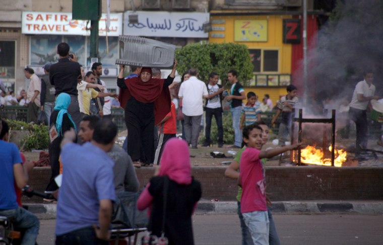 Image: An Egyptian vendor carries her chairs to escape fire following clashes at the center garden where protesters camp at Tahrir Square
