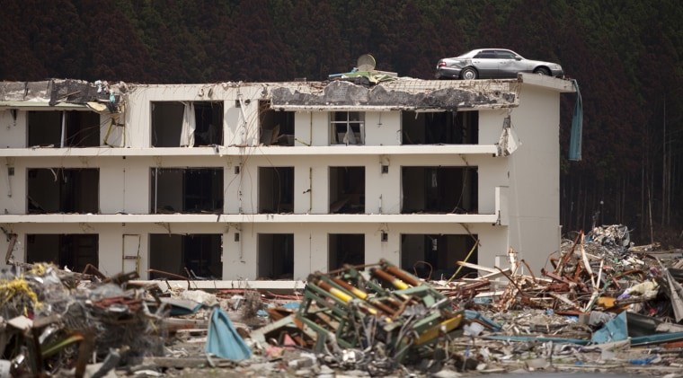 Image:  car sits on the roof of a three story apartment building i