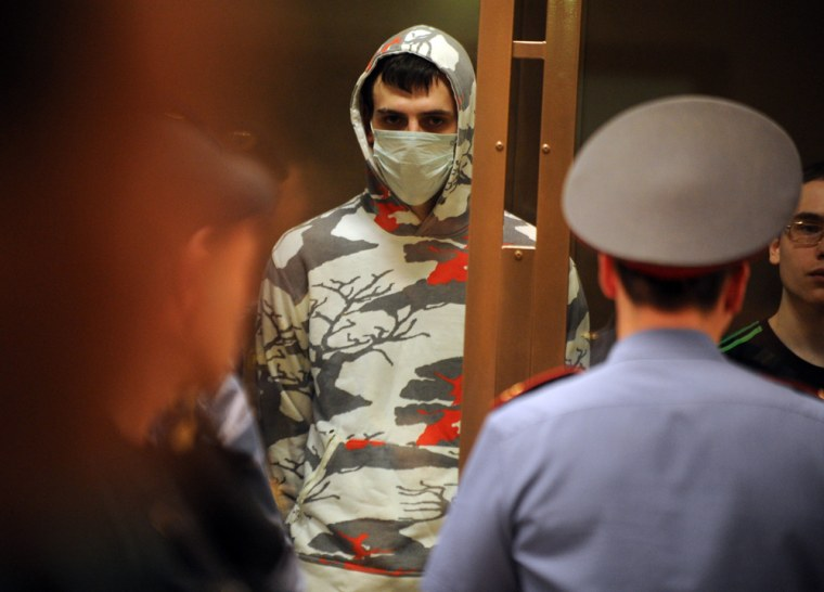 Image: One of the ultra-nationalists accused of two-year murder spree in which 27 members of ethnic minorities were killed stands in court in Moscow