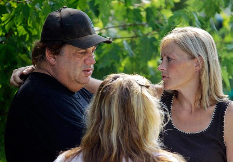 Image: Ellen Vajda, right, comforts Sam Mazzola outside Mazzola's exotic animal sanctuary in Columbia Station, Ohio