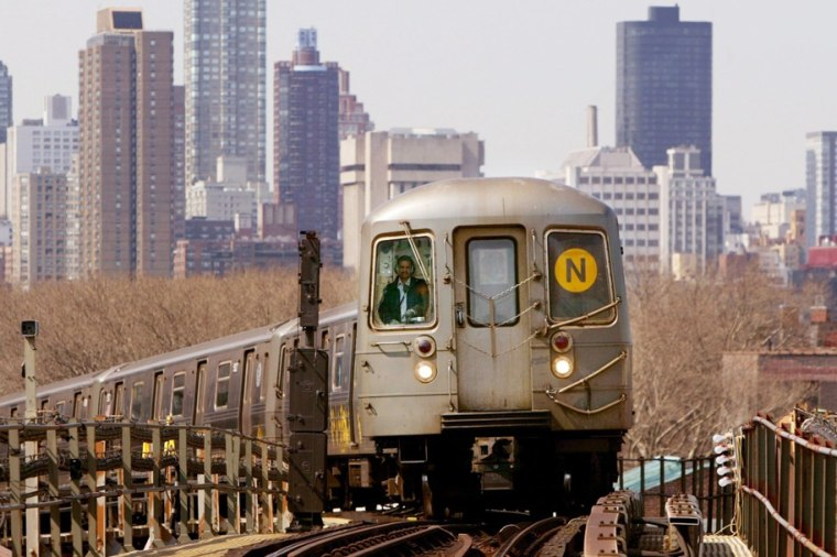 Image: A subway train travels above ground with the Manhattan skyline in the background