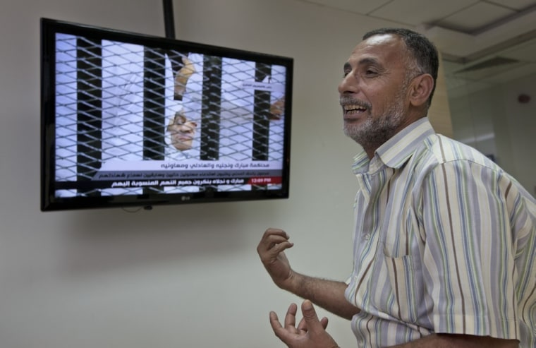 Image: Ramadan Ahmed, 51, whose 16-year-old son Mohammed was shot by police while protesting and killed during Egypt's uprising, reacts upon seeing former Egyptian President Hosni Mubarak on television at his trial,