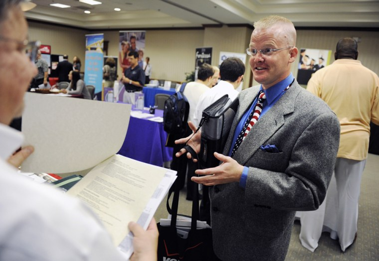 """U.S. Air Force veteran Michael McElroy talks to a recruiter during a \""""Hiring our Heroes\"""" job fair aimed at out-of-work military veterans in Ashburn, Virginia"""