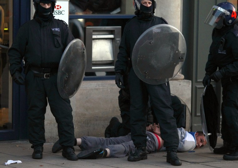 Image: Police officers detain a man in Enfield, north London