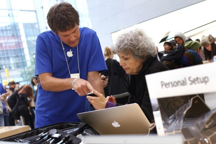 Image: An Apple Store sales associate helps a woman at a Personal Setup station at the Apple store in New York