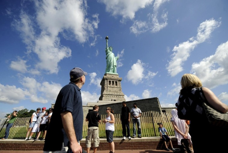Image: Visitors pose for photographs in front of the Statue of Liberty in New York