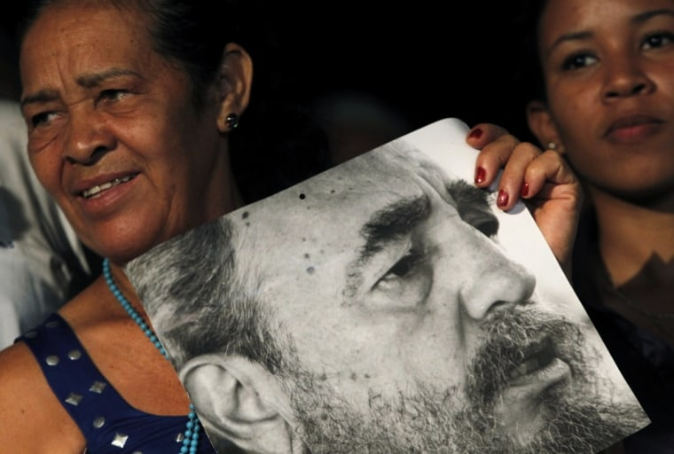 Image: A woman holds a picture of Fidel Castro