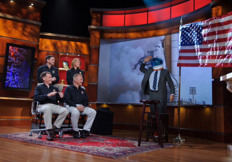 "Stephen Colbert, host of ""The Colbert Report,"" salutes the crew of STS-135 — seated from lower left, commander Chris Ferguson, pilot Doug Hurley and mission specialists Sandy Magnus and Rex Walheim — during their appearance for a taping of his television show on Tuesday evening in New York."