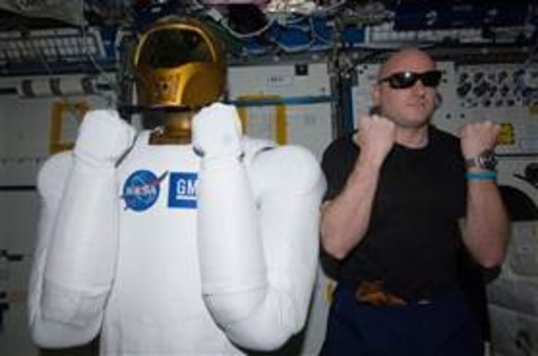 Astronaut Scott Kelly, Expedition 26 commander,poses with Robonaut 2, the dexterous humanoid astronaut helper, in the Destiny laboratory of the International Space Station in this March 15 photo. NASA ground controllers on Monday turned on the robot for the first time since it was delivered to the space station.