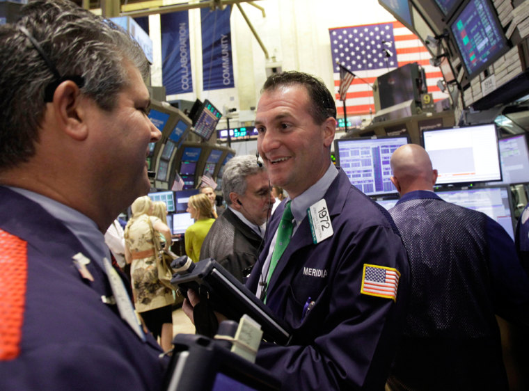 Image: Trader Jonathan Corpina, center, smiles as he works on the floor of the New York Stock Exchange