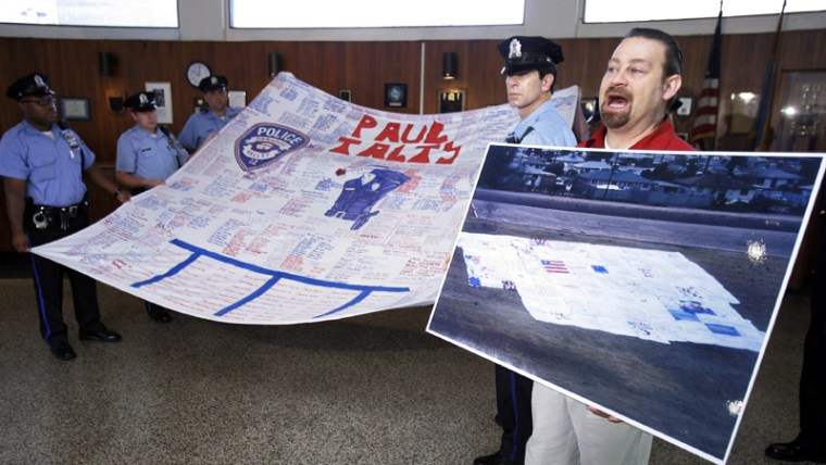 Image: n this Sept. 11, 2007 photo, American Quilt Memorial organizer Kevin Held holds up a photo of several quilts next to members of the Philadelphia Police Department