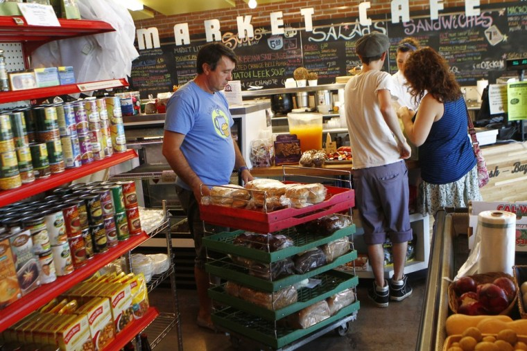 Image: Dino Curovac of Bread Basket Bakery pushes a cart of bread at the Phoenix Public Market in Phoenix