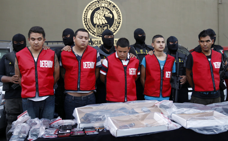 Image: State investigations agents escort five men arrested in connection with an attack on a casino during a presentation in Monterrey
