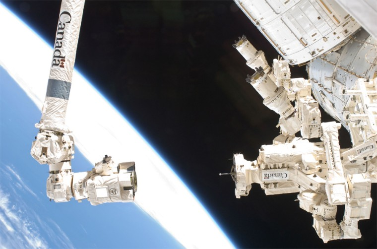 The International Space Station's two-armed robot Dextre is visible on right next to the Canadarm 2 robotic arm.