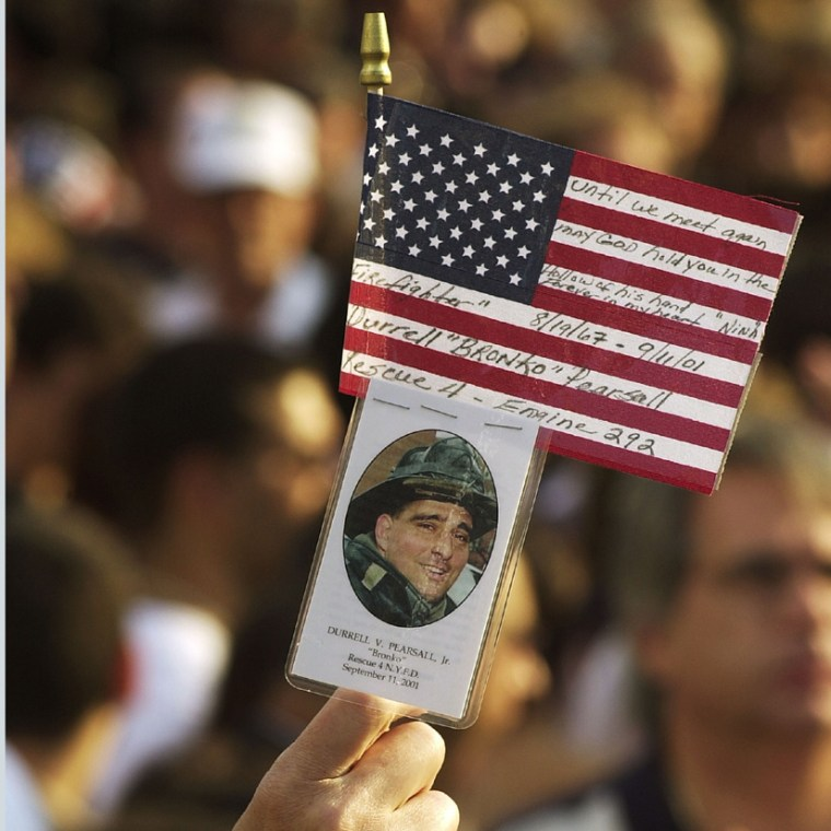 A mourner holds up a picture of a firefighter and an American flag during the World Trade Center memorial service at Ground Zero one year after the attacks.