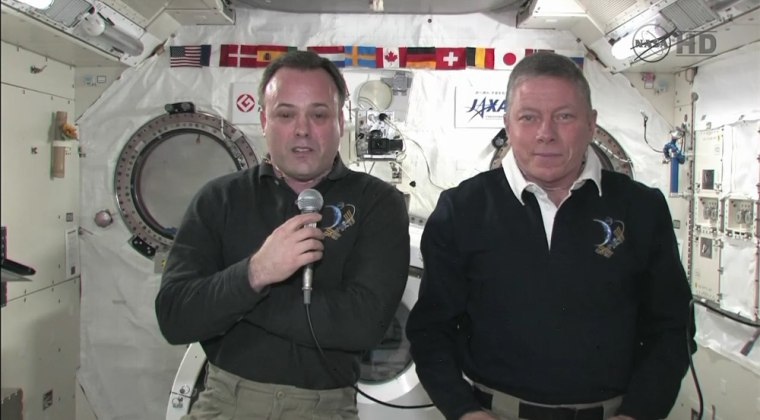 Space station astronauts Ron Garan, left, and Mike Fossum talk to reporters from the International Space Station on Tuesday.