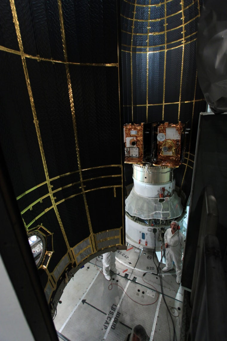 At Space Launch Complex 17B at Cape Canaveralin Florida, the second half of the clamshell-shaped Delta payload fairing swings into place around NASA's twin Gravity Recovery and Interior Laboratory spacecraft under the scrutiny of a spacecraft technician.