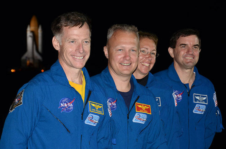 Shuttle Atlantis' final crew, commander Chris Ferguson, pilot Doug Hurley and mission specialists Sandy Magnus and Rex Walheim, stand in front of the orbiter as it rolls out to the launch pad one last time.