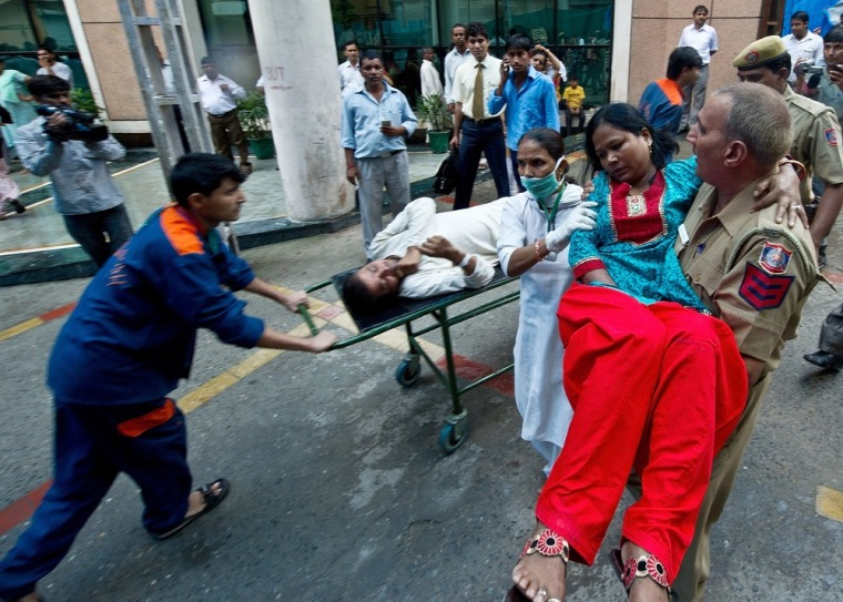 Image: An Indian policeman carries a wounded blast victim following a bomb blast at the Delhi High Court.