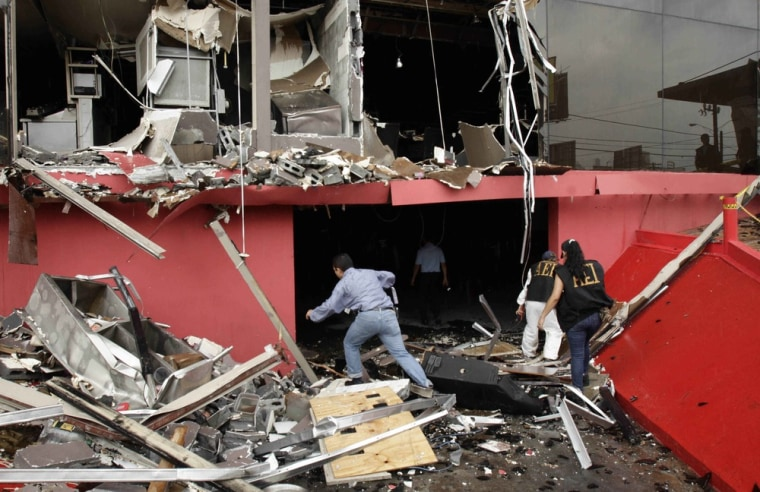 Image: Investigators walk through debris of the charred Casino Royale after a deadly arson assault in Monterrey