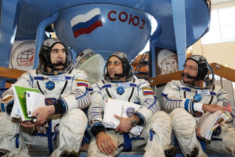 Image: Russian cosmonauts Shkaplerov and Ivanishin and U.S. astronaut Burbank chat after completing exams at the Star City space centre outside Moscow