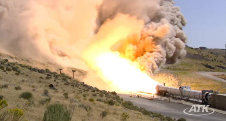 This still photo from an ATK webcast shows a side view of the five-segment solid rocket booster DM3 during a static test firing Thursday at the company's motor proving grounds near Promontory, Utah.