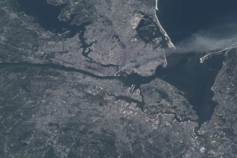 This photo of metropolitan New York City was taken by an Expedition Three crew member onboard the International Space Station on Sept. 11, 2001. A smoke plume rises from the Manhattan area where the World Trade Center was destroyed. The orbital outpost was flying at an altitude of about 250 miles.