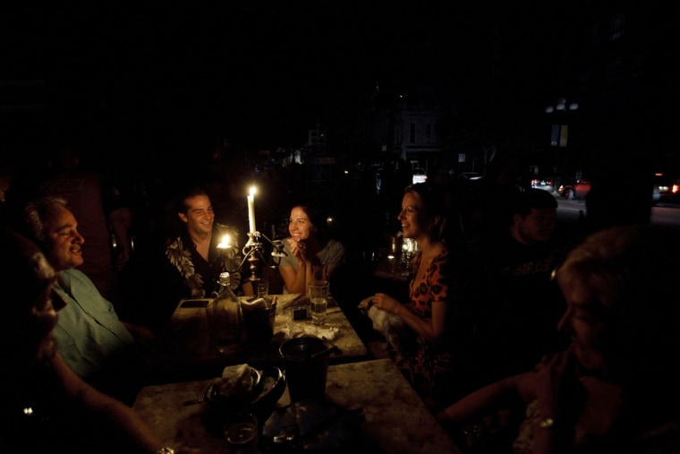 Image: People talk around candles in front of the bar Voyeur in the Gaslamp District during a power outage in San Diego
