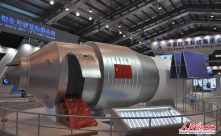 A display model of Tiangong I module is shown at an exhibition hall at the China Academy of Space Technology, complete with access door for public viewing.