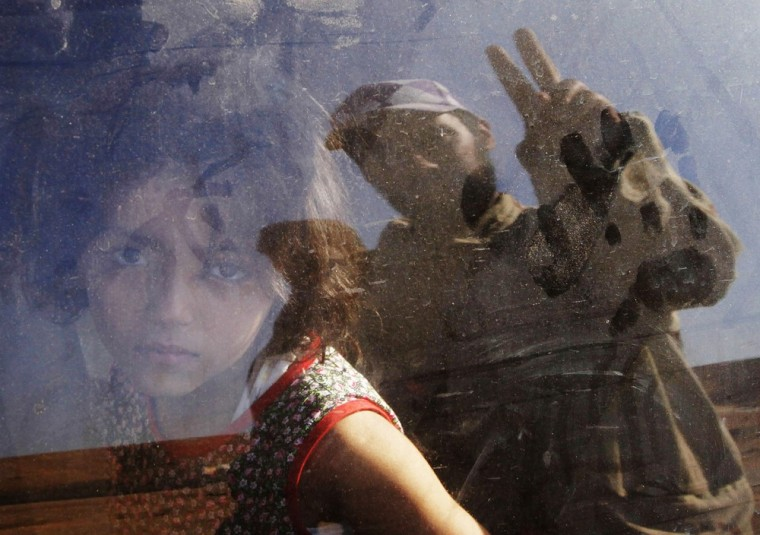 Image: A girl looks at an anti-Gaddafi fighter flashing a victory sign as she flees with her family from the besieged city of Bani Walid