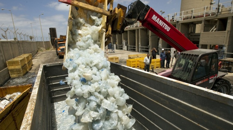 Image: A digger drops jellyfish cleared from the power station in Hadera, Israel